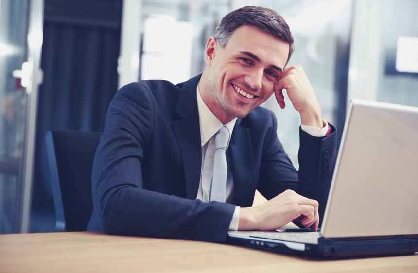 Cheerful businessman sitting with laptop at office-1