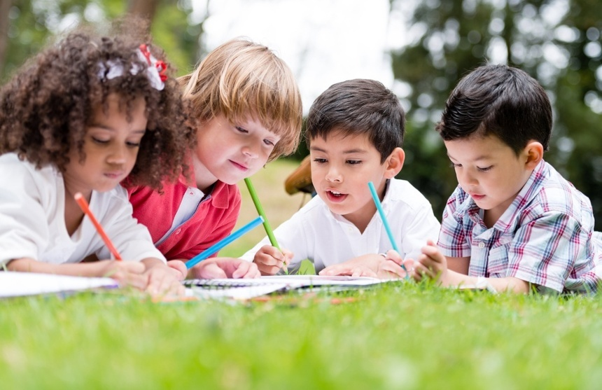 Group of school kids coloring outdoors looking happy.jpeg