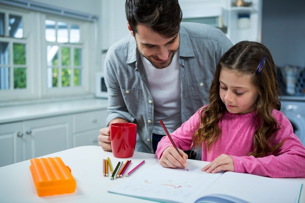 Father helping girl with homework at home in the kitchen