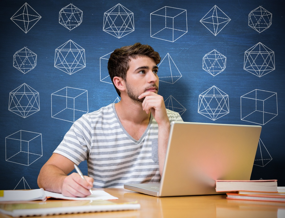 Student studying in the library with laptop against blue chalkboard