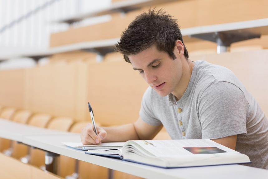 Student sitting reading a book and taking notes in lecture hall
